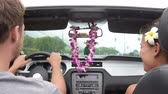 автомобиль : Couple driving car on Hawaii travel with Hula doll dancing on dashboard and lei during road trip. Romantic couple on travel holidays vacation. Man driver behind steering wheel.