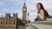 業務 : Woman in London by Big Ben on Westminster Bridge wearing trench coat. Woman enjoying view on Westminster Bridge  London  England  United Kingdom. Multiracial Asian Caucasian female model lifestyle.
