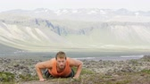 fitness : Push-ups fitness man doing pushups outside in amazing nature landscape on Iceland. Fit male sport model training crossfit outdoors. Caucasian athlete in his 20s. RED EPIC, REAL TIME. Stock Footage
