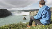 turístico : Iceland tourist relaxing by waterfall Godafoss. Man hiker resting on travel visiting tourist attractions and landmarks in Icelandic nature on Ring Road, Route 1. RED EPIC SLOW MOTION. Vídeos