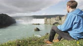 nórdico : Hiker relaxing hiking - waterfall Godafoss Iceland. Man hiker resting on travel visiting tourist attractions and landmarks in Icelandic nature on Ring Road, Route 1.