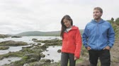 dospělí : Hiking people in nature on Iceland on hike by waterfall Godafoss. Couple enjoying outdoor active healthy lifestyle on travel visiting  landmarks in Icelandic nature. Woman and man. RED EPIC.