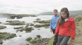 dospělí : Couple hiking in nature on Iceland on hike by waterfall Godafoss. People enjoying outdoor active healthy lifestyle on travel visiting  landmarks in Icelandic nature. RED EPIC. Dostupné videozáznamy
