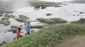 natureza : Hiking couple in nature on Iceland on hike by waterfall Godafoss. People enjoying outdoor active healthy lifestyle on travel visiting  landmarks in Icelandic nature. RED EPIC. Vídeos