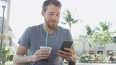 homens : Man sms texting using app on smart phone at cafe drinking iced coffee in city in summer. Handsome young casual man using smartphone smiling happy sitting outdoors. Urban male in his 20s.