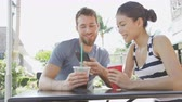 два человека : Couple on cafe looking at smart phone app pictures drinking coffee in summer. Young urban man using smartphone smiling happy to casual asian woman sitting outdoors. Friends in late 20s. Стоковые видеозаписи