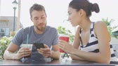casal : Smart phone Cafe couple looking at smartphone screen app laughing having fun on date drinking coffee in summer. Young man using talking with Asian woman sitting outdoors. Friends in late 20s.