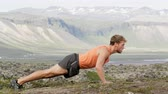 культурист : Fitness sport man doing push-ups outside in nature landscape on Iceland. Fit male sport model training crossfit outdoors doing pushups workout. Caucasian athlete.  RED EPIC SLOW MOTION 90 FPS. Стоковые видеозаписи