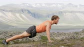 культурист : Fitness pushups man doing push ups outdoors in nature landscape. Fit male sport model training crossfit outside doing push-ups in mountains. Caucasian athlete in his 20s. RED EPIC SLOW MOTION 90 FPS. Стоковые видеозаписи