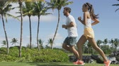выстрел : Running People. Slow motion video of multiethnic young couple jogging in park. Full length of man and woman are in sports clothing. They are representing their healthy lifestyle.
