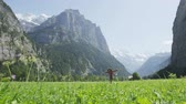 женщины : Woman dancing having fun in happy grass field in Switzerland Swiss Alps. Girl laughing swirling around in Lauterbrunnen valley with Jungfrau, Eiger and Monch mountains in background. RED EPIC Footage. Стоковые видеозаписи