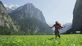 schweiz : Happy woman having fun running in field nature excited of joy happiness. Joyful active lifestyle with free girl enjoying freedom, Lauterbrunnen valley, Swiss Alps, Switzerland. RED EPIC SLOW MOTION