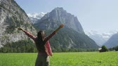 seyahat : Happy free woman with arms raised in freedom nature excited of joy happiness. Cheerful active lifestyle with girl serene rasing arms in Lauterbrunnen valley, Swiss Alps, Switzerland, Europe. Stok Video