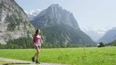 природа : Woman hiking in Switzerland alps landscape. Female hiker tourist on hike in Swiss alpine amazing nature landscape in Lauterbrunnen valley in Bernese Oberland, Schweiz, Europe. RED EPIC SLOW MOTION. Стоковые видеозаписи