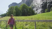 schweiz : Hiking in Switzerland alps by waterfall Staubbach falls. Woman hiker walking in Swiss alpine nature landscape in Lauterbrunnen valley in Bernese Oberland, Schweiz, Europe. RED EPIC SLOW MOTION.