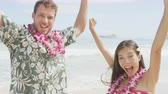 menina : Cheering celebrating winning couple on Hawaii beach beach on Hawaiian vacation. Asian woman and Caucasian man wearing flower lei garland and Aloha clothing raising arms up dancing of joy. RED EPIC. Vídeos