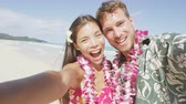líbánky : Couple on beach taking selfie photo on Hawaii with smart phone.  Young woman and man in love using smartphone on beach vacations in Hawaiian clothing wearing Aloha shirt dress and flower lei. RED EPIC