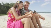 telemóvel : Couple on beach using smart phone app sharing photos on social media on Hawaii with smart phone.  Young woman and man in love on beach vacations in Hawaiian clothing flower lei. RED EPIC. Vídeos