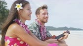spirit : Man on beach playing ukulele instrument on Hawaii with having fun. Young couple, woman and man in love on beach vacations in Hawaiian clothing wearing Aloha shirt dress and flower lei. RED EPIC. Stock Footage