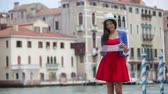 mixed race : Travel tourist woman with camera and map in Venice, Italy. Vintage retro style Asian girl on vacation smiling happy by Grand Canal. Mixed race Asian Caucasian girl having fun traveling outdoors.