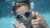 mulheres : Woman swimming underwater in pool smiling happy giving thumbs up sign hand waving hands saying hello looking at camera. Young female swimmer with swim goggles at holiday resort.