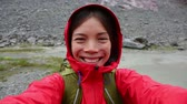 aplicativo : Active outdoors hiker taking selfie using app on smartphone. Happy hiker with mobile phone outside in nature in rain. Girl on hike in mountains. Vídeos