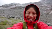 sorriso : People having fun. Active outdoors hiker taking selfie using app on smartphone. Happy hiking girl with mobile phone outside in nature in rain. Girl on hike in mountains.