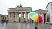alemão : Brandenburg Gate Berlin Germany people. Woman at Brandenburg Gate or Brandenburger Tor standing with umbrealla in rain in Berlin, Germany during travel in Europe.