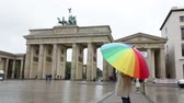 alemão : Berlin people - woman at Brandenburg Gate or Brandenburger Tor standing with umbrealla in rain in Berlin, Germany during travel in Europe.