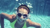 sensualidade : Video of young woman swimming in pool. Beautiful woman is wearing goggles. She is gesturing thumbs up in swimming pool. Vídeos