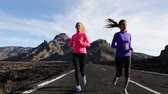 lifestyle shot : Young women jogging on mountain road. Female runners are in sportswear. Multiethnic joggers are representing their healthy lifestyle. Stock Footage