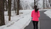 снег : Running running. Rear view of woman running on road in winter snow. Young female is in sportswear. Runner jogging in cold weather. Girl living healthy active lifestyle working out outside. Стоковые видеозаписи