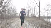 consciente : Sporty young woman running on footpath amidst bare trees. Determined female is in sportswear. Confident runner jogging in countryside. She is representing her healthy lifestyle. Vídeos