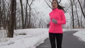 workout : Winter cardio exercise - woman jogging doing her workout outside. Young adult running in outdoor park with snowy forest background wearing cold weather gear. Stock Footage
