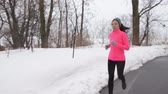 chlad : Winter jogging - young Asian Chinese adult woman runner running breathing cold air wearing pink windbreaker jacket, headband and gloves doing a cardio workout.