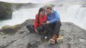 assistindo : Happy young couple watching photographs on smartphone at Godafoss waterfall. Cheerful male and female tourists are sitting on cliff. Man and woman are visiting famous places in Iceland.