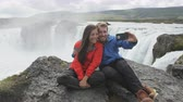 telemóvel : Happy young couple taking selfie with smartohone against majestic Godafoss waterfall. Cheerful male and female tourists sitting on cliff. Man and woman visiting famous tourist attraction of Iceland.