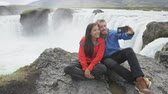 seyahat : Cheerful couple posing for selfie on smart phone against majestic Godafoss waterfall. Happy male and female tourists are sitting on cliff. Man and woman are at famous tourist attraction of Iceland.