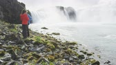 wodospad : Young multiethnic tourist couple hiking at Godafoss waterfall. Woman is photographing spectacular waterfall through smartphone. Tourists are enjoying vacation at beautiful waterfall in Iceland.