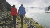 utazási : Couple visiting majestic Godafoss waterfall. Man and woman are on vacation at beautiful waterfall in Iceland. Male and female tourists are walking at famous attraction. Stock mozgókép