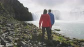 brasão : Young couple walking at majestic Godafoss waterfall. Man and woman are visiting beautiful waterfall in Iceland. Male and female tourists are at famous attraction. Stock Footage