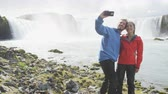 мобильный : Smiling young couple photographing against spectacular Godafoss waterfall. Male and female tourists are taking selfie during vacation at Iceland. Man and woman are visiting famous tourist attractions. Стоковые видеозаписи