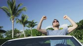 pessoas : Enthusiastic young happy man cheering while sitting in convertible car. Male driver is clenching fists while celebrating success in car. Handsome man driving wearing sunglasses against blue sky. Stock Footage