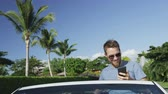 автомобиль : Happy young man taking smartphone selfie while sitting in convertible car. Handsome male model is smiling while photographing himself using mobile cell smart phone. Shot on RED EPIC.