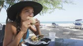 hambúrguer : Smiling young woman eating burger sliders food at beach. Young female is sitting at outdoor restaurant. Beautiful tourist in bikini and sunhat is on her summer vacation on Dover Beach, Barbados. Stock Footage