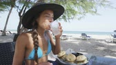 insalubre : Happy young woman drinking water at beach restaurant. Young female is eating snacks sitting at outdoor table. Beautiful tourist in bikini and sunhat is on summer vacation on Dover Beach, Barbados. Vídeos