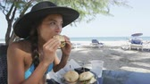 hambúrguer : Beautiful young woman eating sandwich at beach restaurant. Young female is enjoying snacks sitting at table. Beautiful tourist in bikini and sunhat is on her summer vacation on Dover Beach, Barbados. Stock Footage