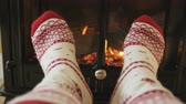 lenha : Winter concept. Woman feet warming in front of fireplace. She is wearing socks nearby burning stove. Female is relaxing in living room during winter