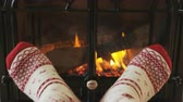 ушлый : Feet in socks warming by fire in fireplace. Girl is wearing socks nearby fireplace. Female is relaxing at home during winter. SLOW MOTION.