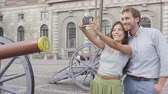 escandinavo : Selfie tourists couple taking photo picture with smartphone of Stockholm Royal Palace, Sweden, Europe. Happy tourist people visiting landmark attractions in Gamla Stan, the old town of Stockholm. Stock Footage